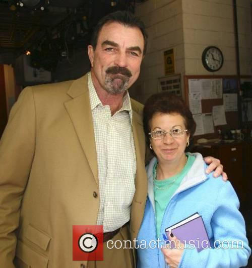 Tom Selleck posing with a fan outside the...