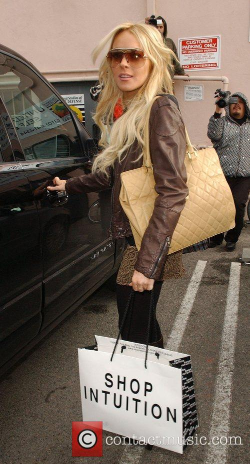 Lindsay Lohan in high spirits carrying a large...
