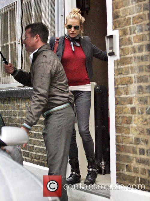 Sienna Miller rushes from her house in the...