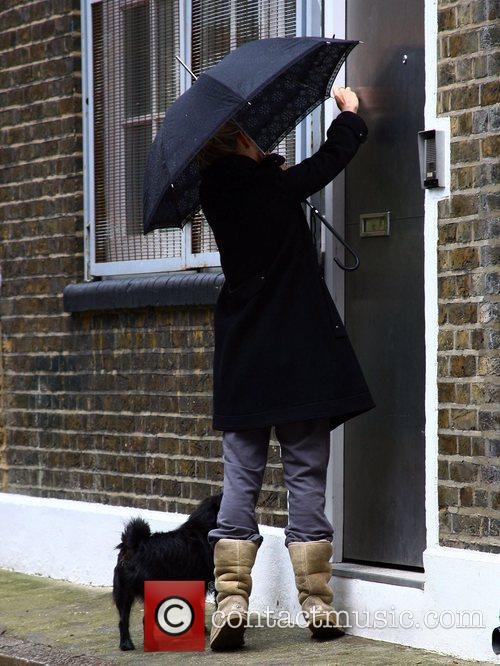 Sienna Miller  hides under her umbrella as...