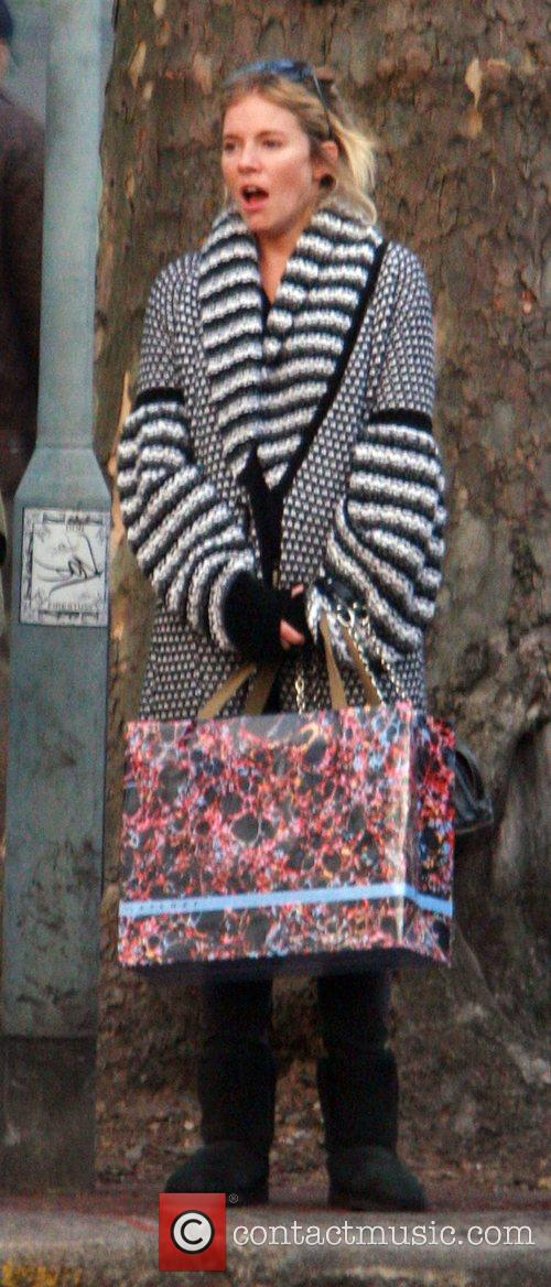 Sienna Miller waits for a taxi after visiting...