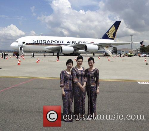Singapore Airlines flight attendants in front of the...