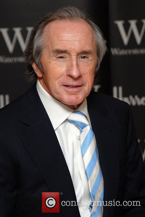 Sir Jackie Stewart signs copies of his new...