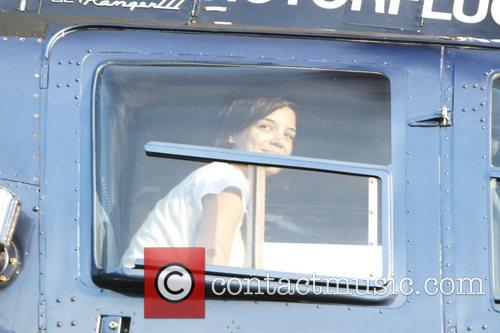 Katie Holmes boarding a helicopter on a sports...