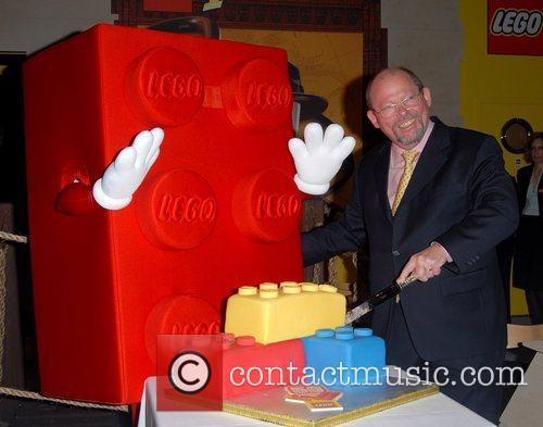 The Danish Ambassador Birger Riis-Jorgenson cutting a cake...