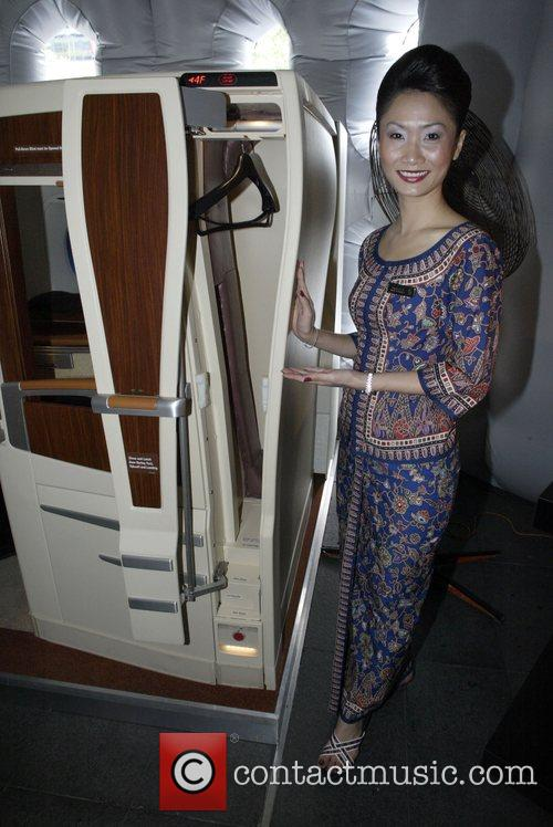 Singapore Airlines flight stewardess Kayla Yap demonstrates passenger...