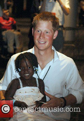 Prince Harry holds 3 year old Eufrafina (the...