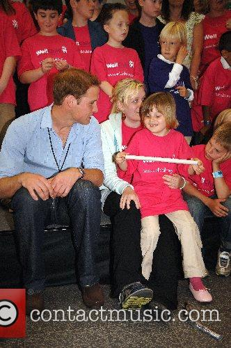 Prince William sits and poses with children being...