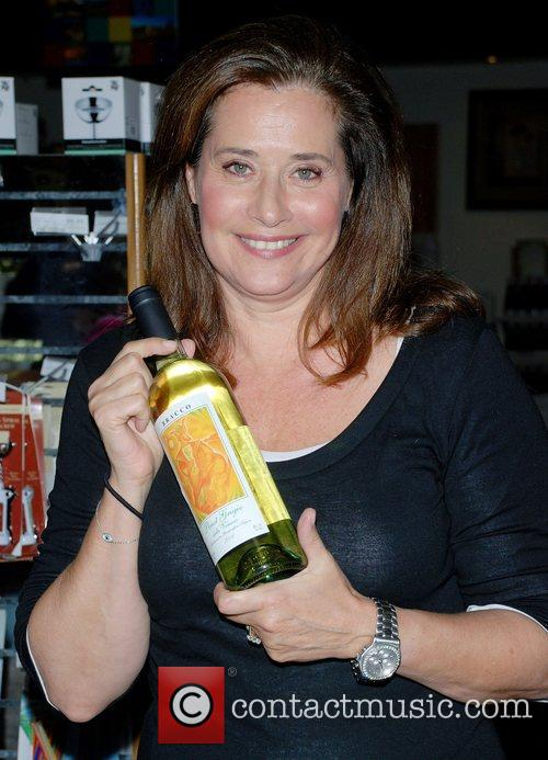 Lorraine Bracco signs bottles of her wine for...