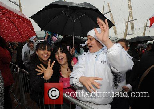 X-Factor hopefuls suffer the torrential rain as they...