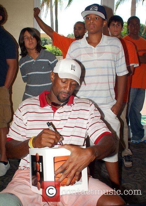Alonzo Mourning signs a basketball watched by his...
