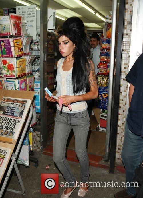Amy Winehouse emerges from a newsagent clutching a...