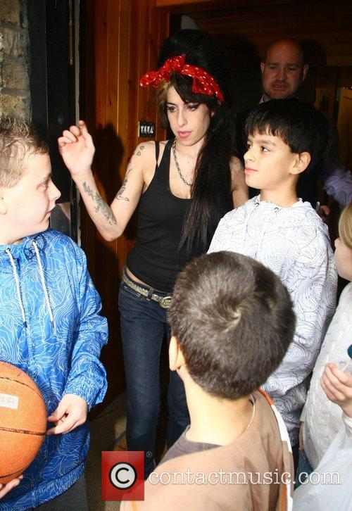 Amy Winehouse Poses for photos with young fans,...