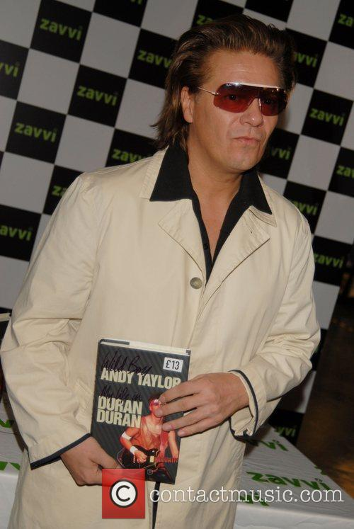 Andy Taylor of Duran Duran signing copies of...
