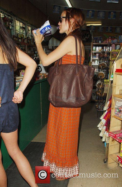 Showing off her baby bump while stopping at...