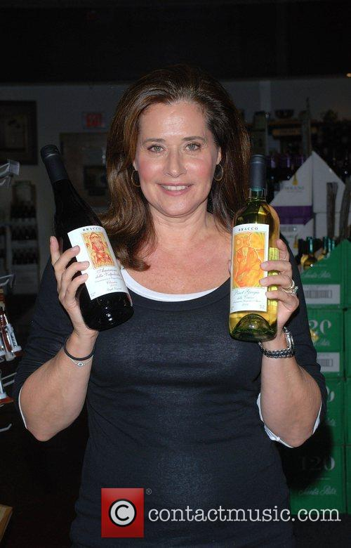 Signs bottles of her wine for fans at...
