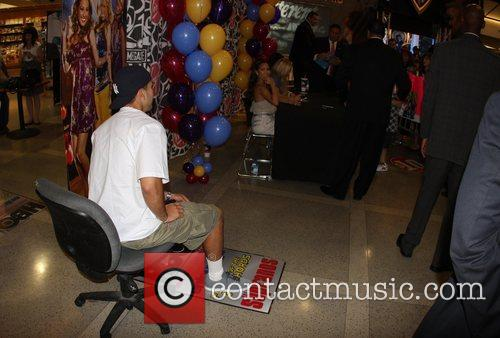 Robert Kardashian watches his girlfriend Adrienne Bailon sign...