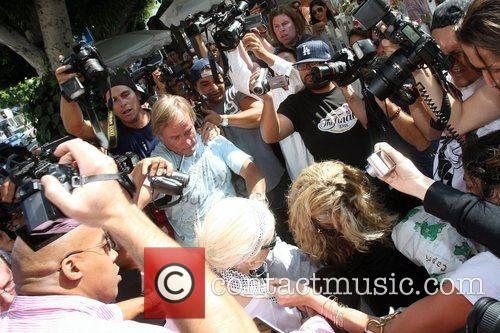 Christina Aguilera is mobbed by the paparazzi as...