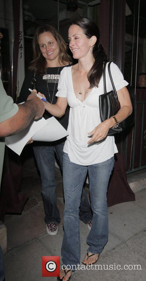 Courteney Cox stops to sign her autograph for...