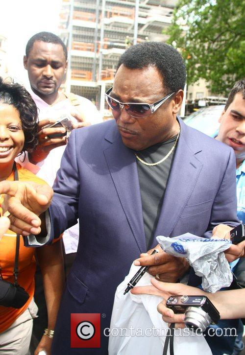 George Benson signs autographs for fans outside the...