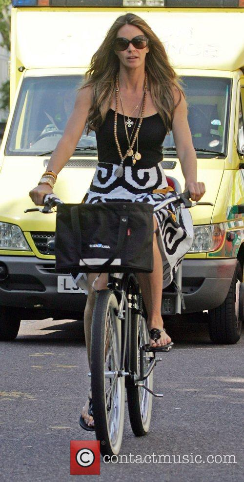 Elle Macpherson rides her bicycle through a very...