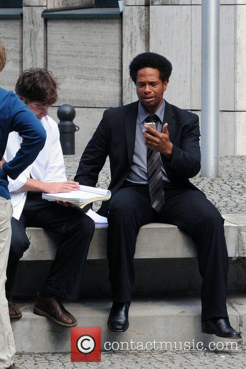Gary Dourdan is looking at his iPhone at...