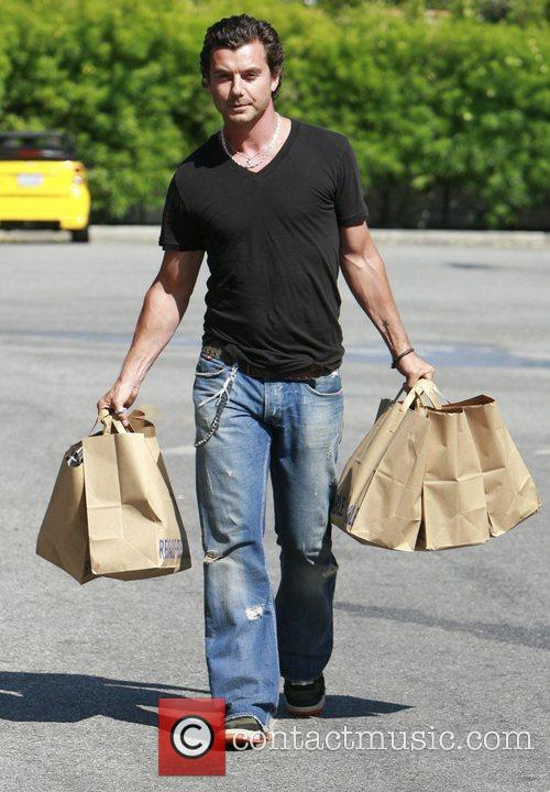 Gavin Rossdale is laden with bags as he...