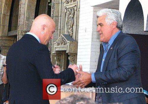 Jay Leno congratulates Howie Mandel on receiving a...