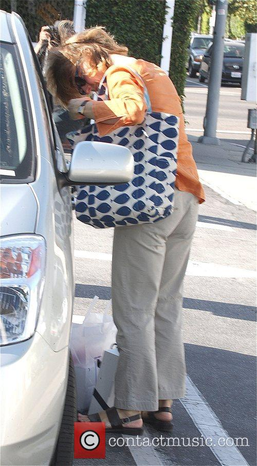 Jodie Foster hides behind shopping bags as she...