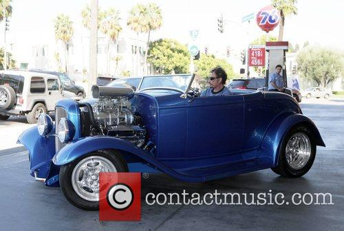 Refuels his custom supercharged roadster at a 76...