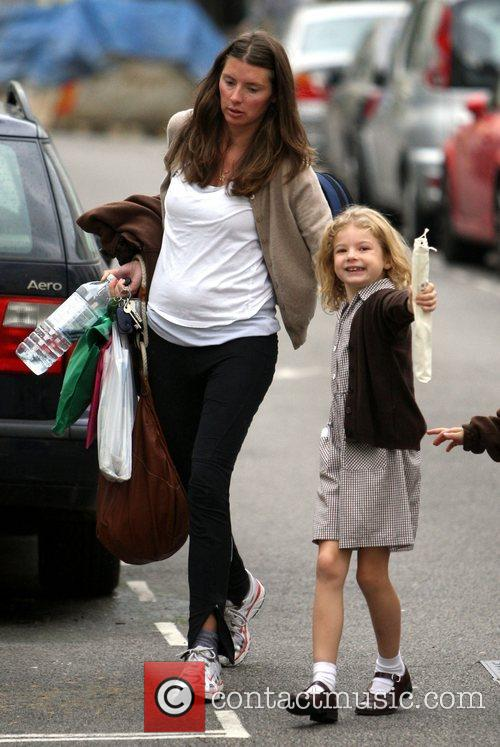 Shows off her new baby bump after she...