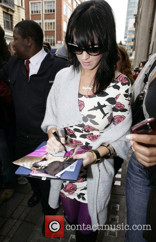 Katy Perry stops to sign autographs as she...