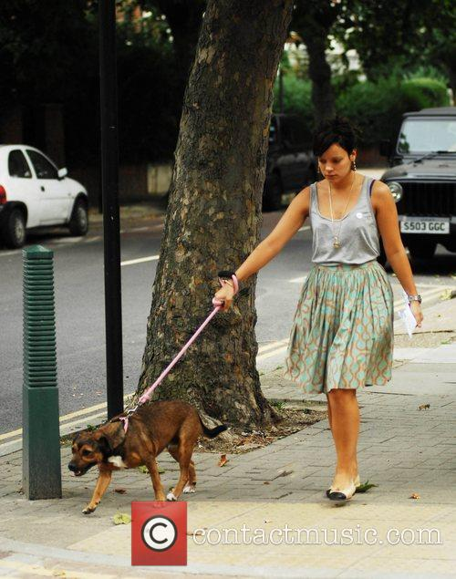 Looking unhappy as she takes her dog for...