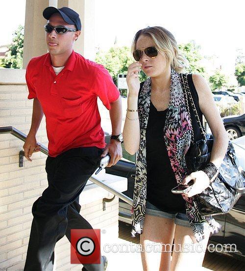 Lindsay Lohan enters Barneys New York as she...