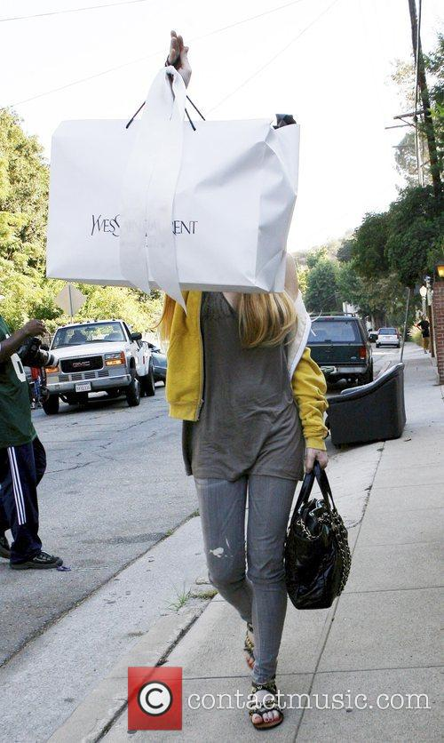 Lindsay Lohan covers her face with an Yves...