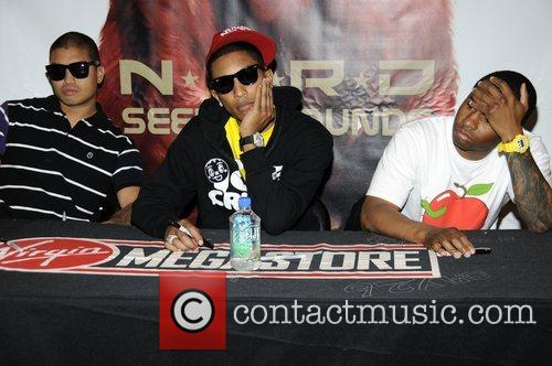 N.E.R.D. signs copies of their latest CD 'Seeing...