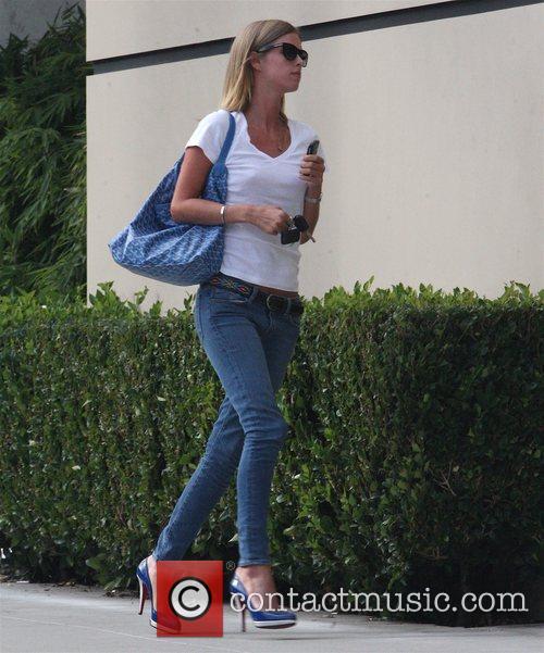 Nicky Hilton talks into her cellphone as she...