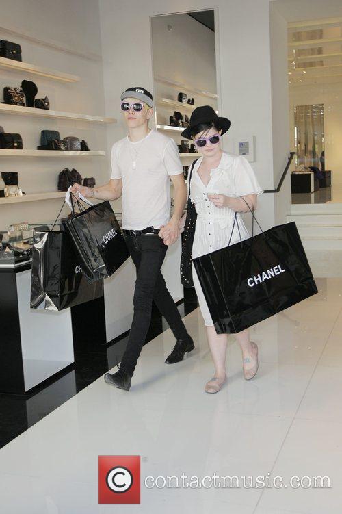 Luke Howell and Kelly Osbourne holding hands at...