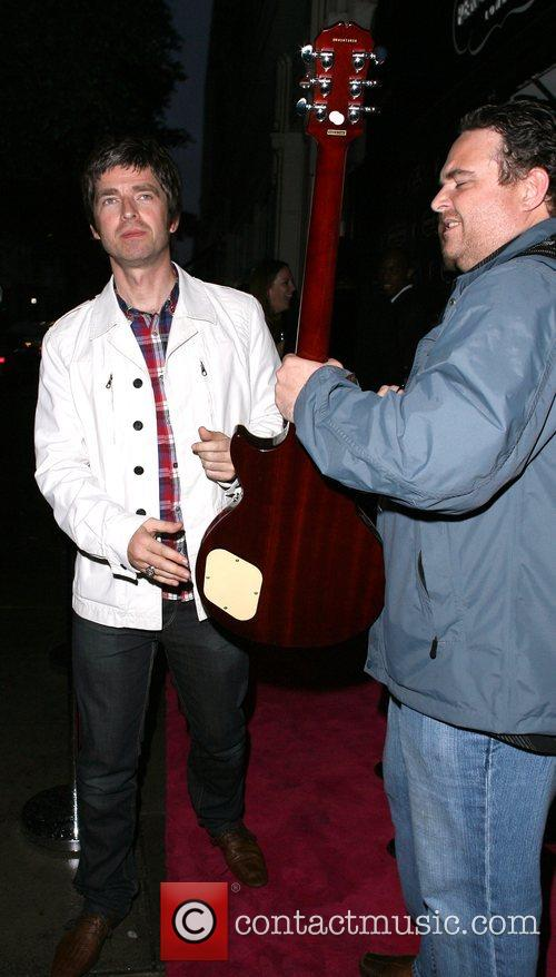 Noel Gallagher signs a photographers guitar as he...