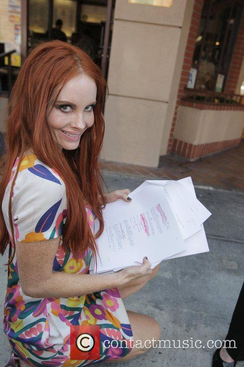 Phoebe Price shows photographers some scripts for upcoming...