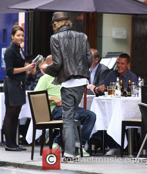 A scruffy looking Rhys Ifans enjoying a few...