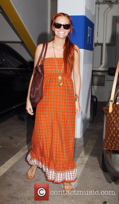 Showing off her baby bump while heading to...