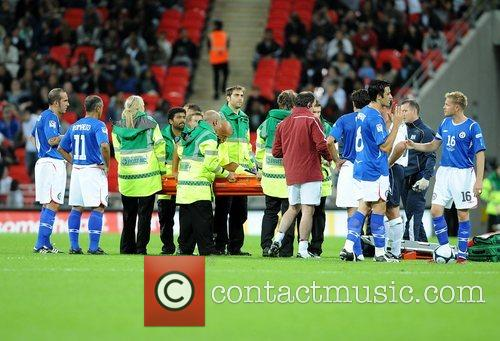 Injured referee Pierluigi Colina is stretchered off Soccer...