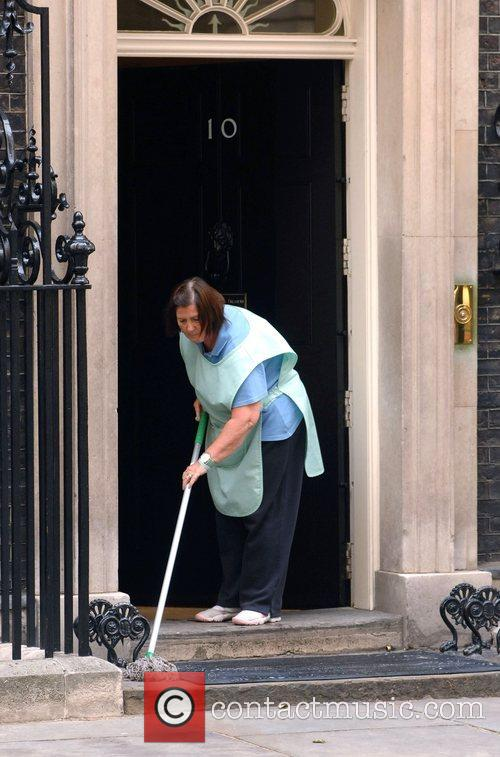 A Cleaning leady mops the entrance to 10...