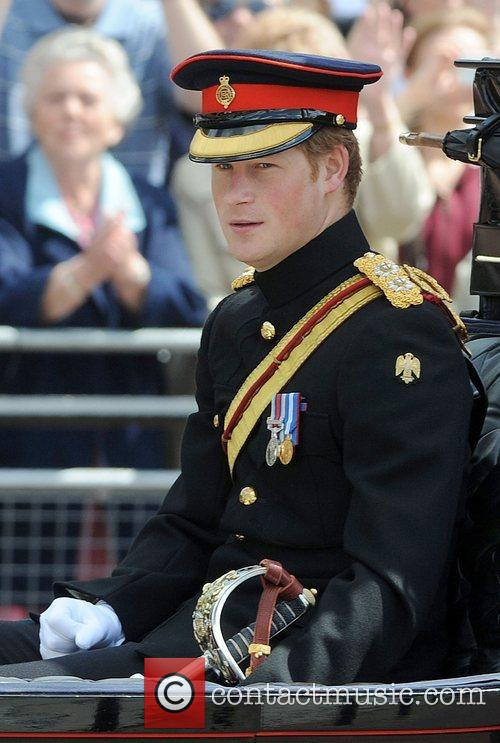 Prince Harry rides in a coach through the...