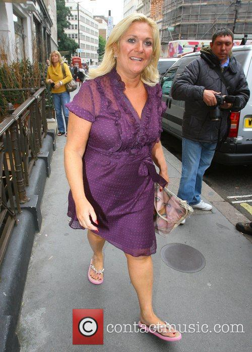 Wearing a purple dress and flip-flops as she...