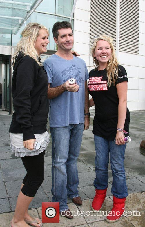 Simon Cowell posing with fans X Factor judges...