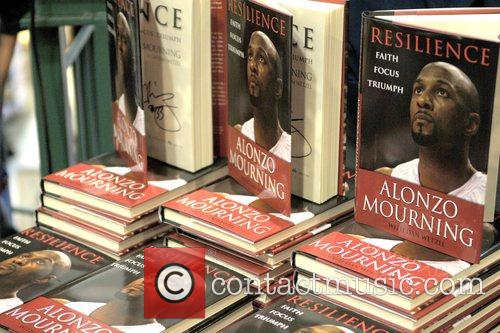 Atmosphere NBA champion Alonzo Mourning signs copies of...