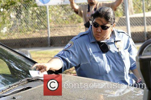 A Policewoman puts a parking ticket on Alyson...