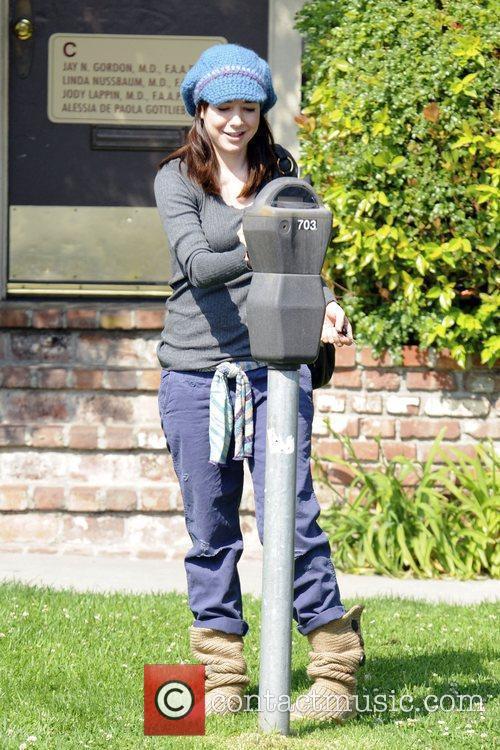 Alyson Hannigan puts money in a parking meter...
